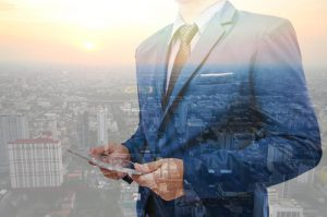 Double exposure of business man using tablet over the city